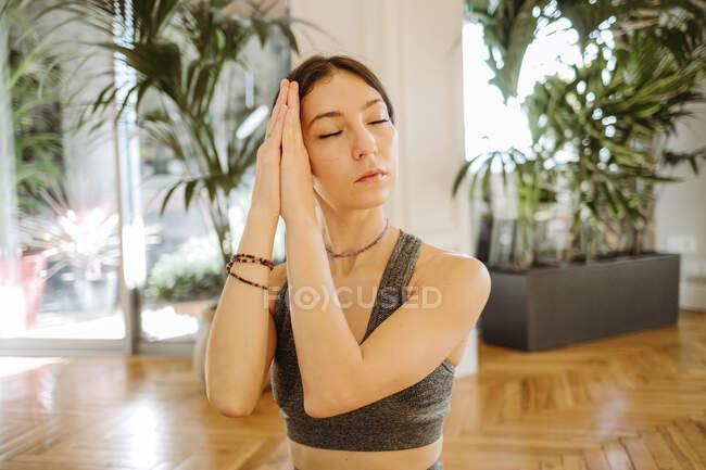 Красивая женщина медитирует с сжатыми руками дома — стоковое фото