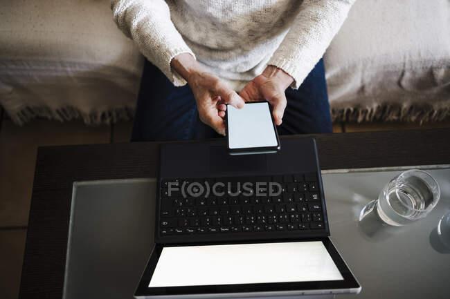 Старшая женщина с ноутбуком с помощью мобильного телефона, сидя на диване дома — стоковое фото