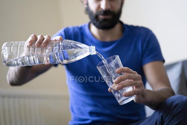 Жаждущий молодой человек наливает воду в стакан дома — стоковое фото