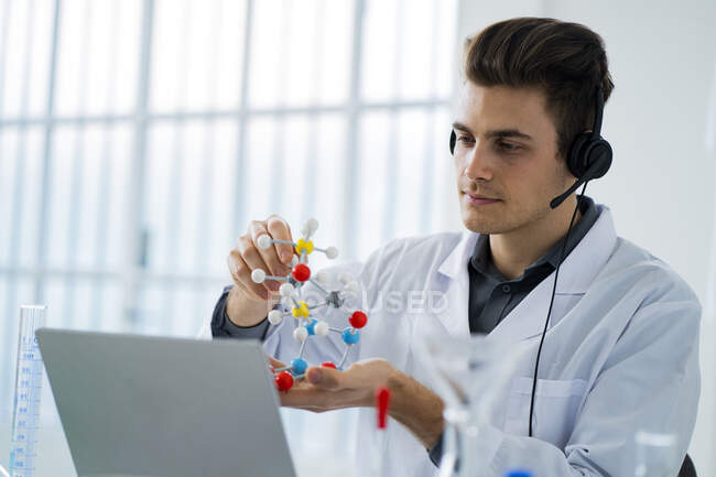 Jeune scientifique masculin tenant la structure moléculaire lors d'un appel vidéo en laboratoire — Photo de stock