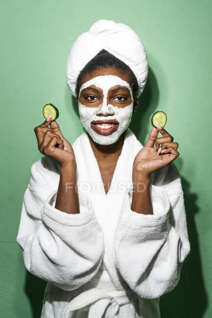 Jovem mulher com máscara facial segurando pepino enquanto está de pé contra o fundo verde — Fotografia de Stock