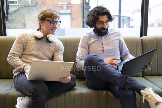 Чоловіки - підприємці, які працюють на ноутбуці, сидячи на дивані в офісі співпрацівників. — стокове фото