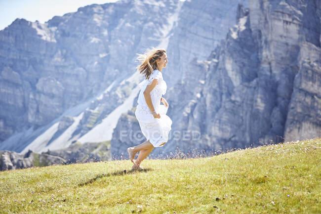 Активна жінка біжить по луці в сонячний день. — стокове фото