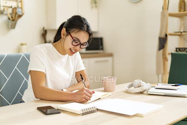 Mulher sorridente escrevendo em livro em casa — Fotografia de Stock