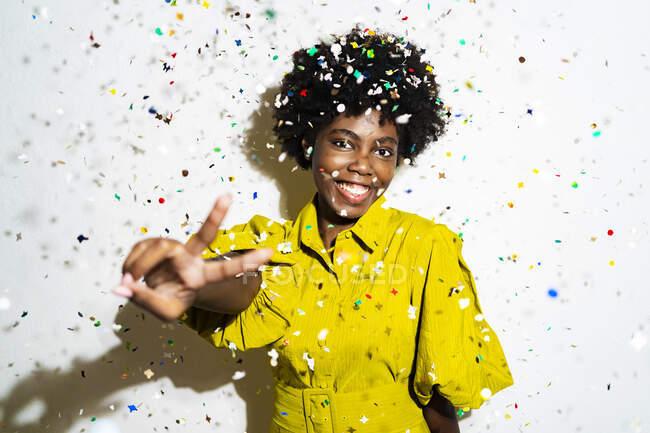 Allegro donna capelli ricci mostrando segno di pace mentre in piedi in mezzo a coriandoli sullo sfondo bianco — Foto stock