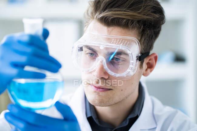 Hombre guapo científico examinando química en laboratorio - foto de stock