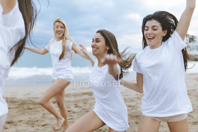 Carefree female friends with arms outstretched enjoying at beach during vacations — Stock Photo