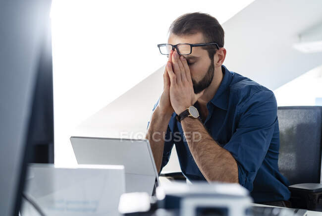 Empresario sentado con la cabeza en las manos en la oficina - foto de stock