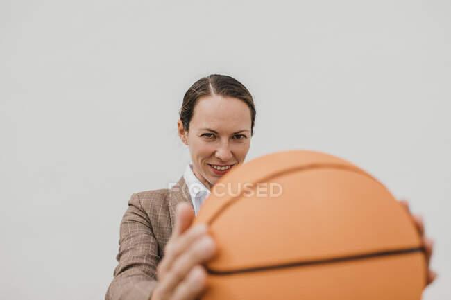 Profissional feminino sorridente com basquete durante o intervalo — Fotografia de Stock