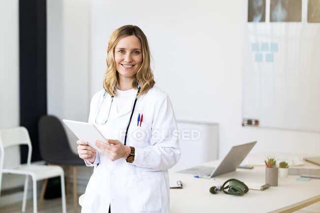 Médico femenino adulto medio con tableta digital apoyada en el escritorio mientras está de pie - foto de stock