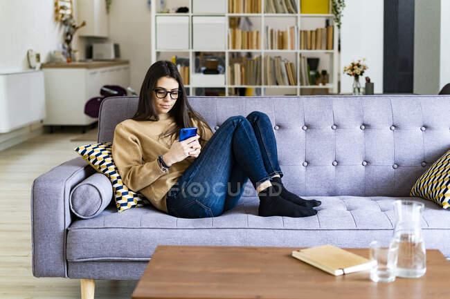 Mujer joven usando el teléfono móvil mientras está sentada descansando en el sofá en casa - foto de stock