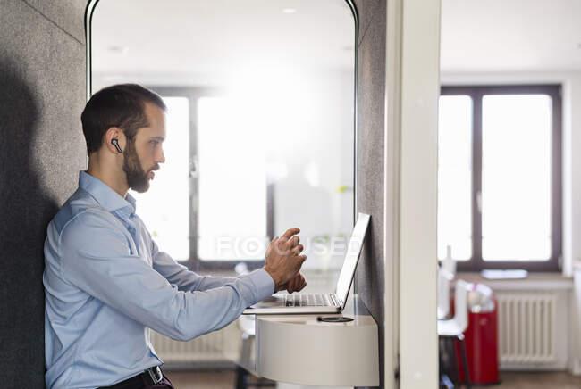 Бізнесмен, який приходить на зібрання на ноутбуці, сидячи в телефонній будці при офісі. — стокове фото
