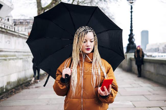 Жінка з парасолькою під час ходьби по дорозі. — стокове фото