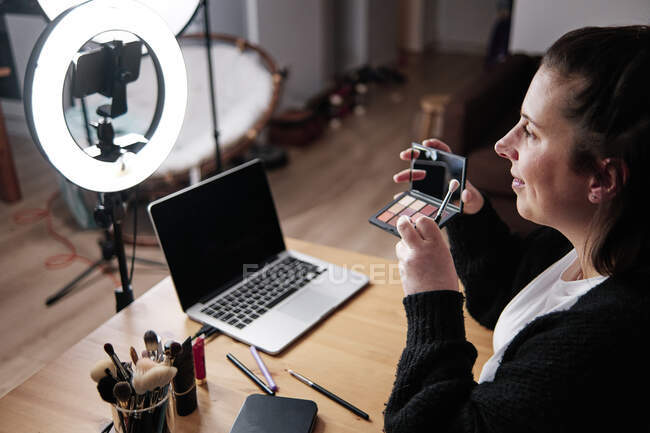 Smiling woman holding Make-up Palette while recording make-up tutorial at home — Stock Photo