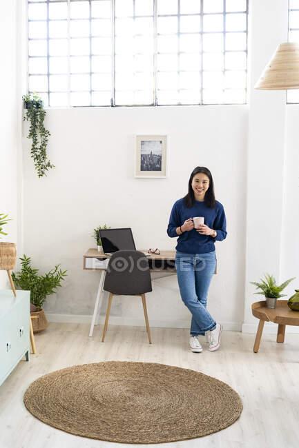 Жінка з чашкою кави спирається на стіл у домашньому кабінеті. — стокове фото