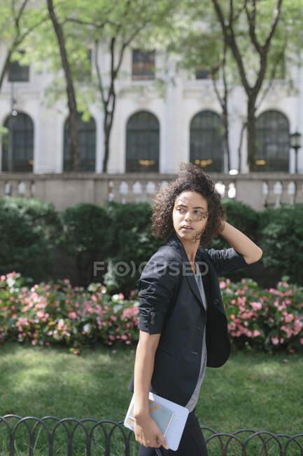 Jovem profissional feminino com a cabeça na mão olhando para longe enquanto caminhava perto de plantas — Fotografia de Stock