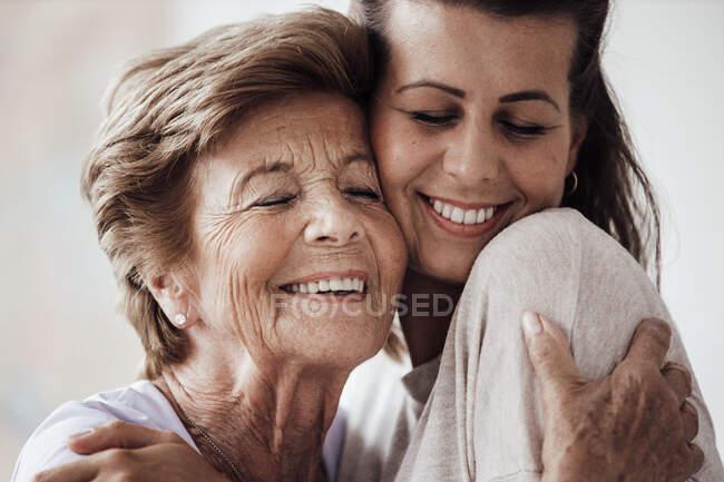 Feliz joven mujer y abuela abrazándose en casa - foto de stock