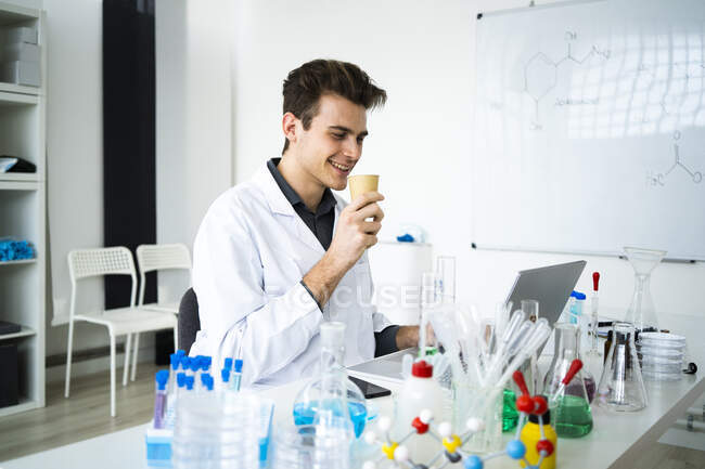 Smiling male scientist having coffee while working on laptop in laboratory — Stock Photo