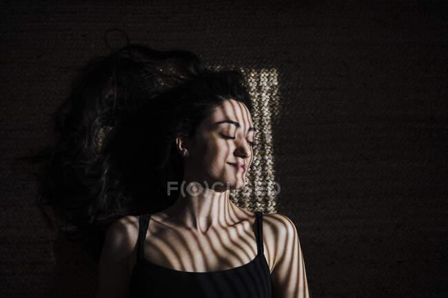 Улыбающаяся женщина с тенью жалюзи спит на джуте дома — стоковое фото