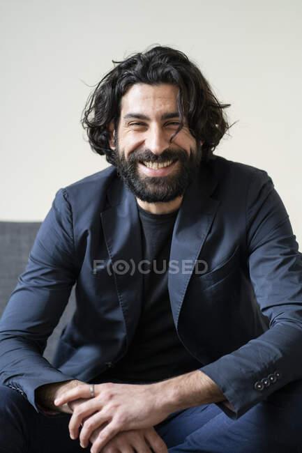 Bärtiger Mann lächelt auf Sofa — Stockfoto