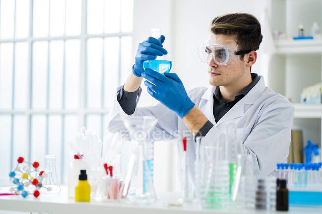 Young scientist measuring chemical in flask at laboratory — Stock Photo