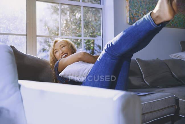 Mujer feliz abrazando almohada mientras descansa en el sofá en casa - foto de stock