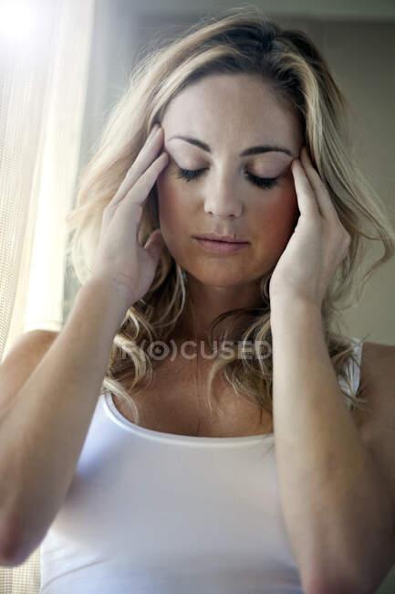 Mujer joven con dolor de cabeza en casa - foto de stock