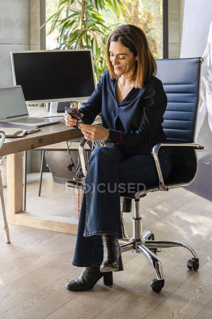 Улыбающаяся женщина-предприниматель с помощью смартфона, сидя на стуле в офисе — стоковое фото