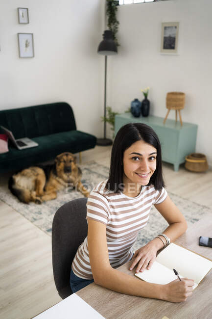 Посмішка молодої жінки з ручкою і записницею сидять за столом у вітальні. — стокове фото