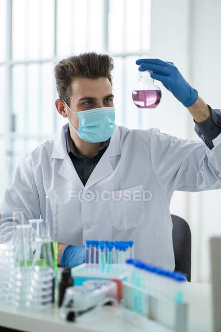 Male scientist analyzing chemical in flask during COVID-19 — Stock Photo