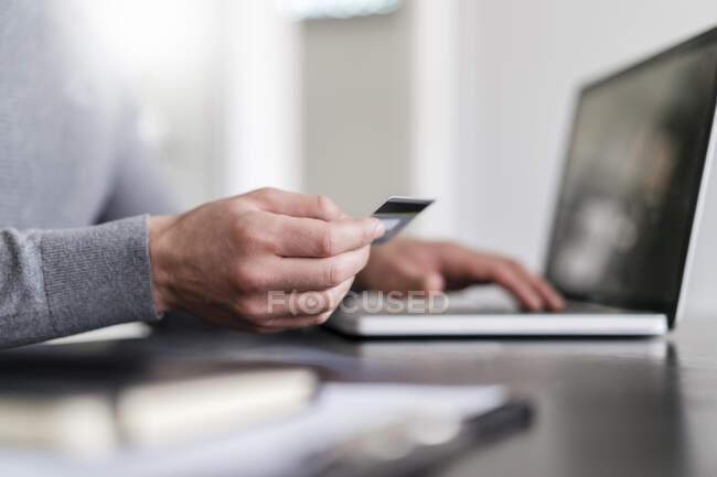 Мужские руки предпринимателя онлайн оплаты через кредитную карту на ноутбуке в офисе — стоковое фото