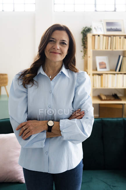 Smiling mature businesswoman with arms crossed standing at home — Stock Photo