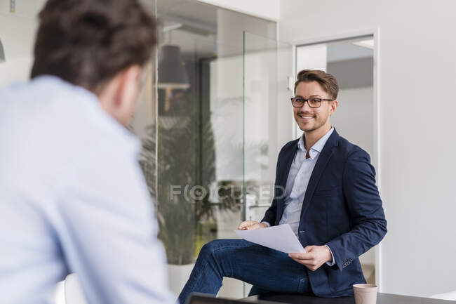 Male entrepreneur smiling while discussing with colleague in office — Stock Photo