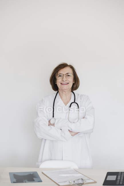 Médico sonriente con los brazos cruzados de pie frente al escritorio en el hospital - foto de stock