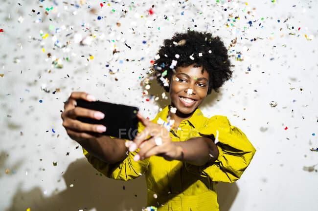 Giovane donna che prende selfie attraverso il telefono cellulare mentre in piedi in mezzo a coriandoli sullo sfondo bianco — Foto stock