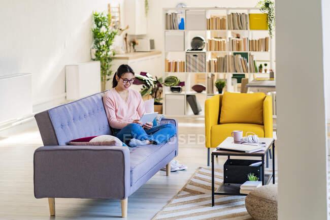Жінка користується цифровою табличкою, сидячи вдома. — стокове фото