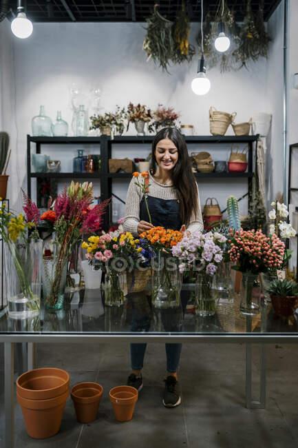 Улыбающаяся цветочница, работающая в цветочном магазине — стоковое фото