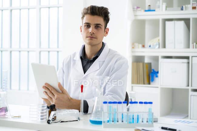 Jeune homme scientifique tenant une tablette numérique assis au bureau en laboratoire — Photo de stock
