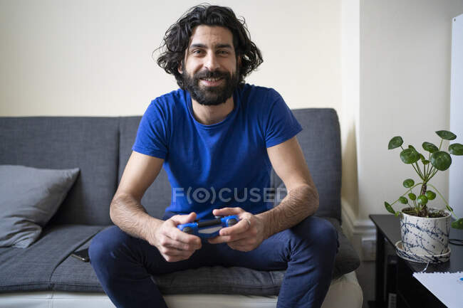 Smiling man with game controller sitting on sofa at home — Stock Photo