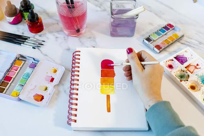 Mulher pintura popsickle sorvete com aquarela no livro na mesa — Fotografia de Stock