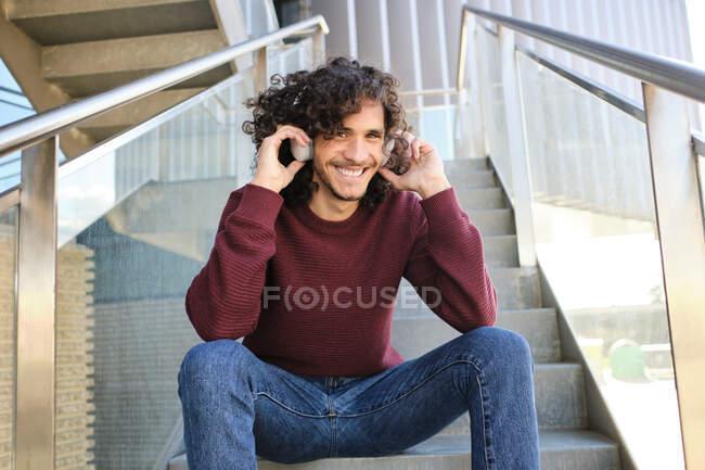 Улыбающийся молодой человек в наушниках сидит на ступеньках офисного здания — стоковое фото
