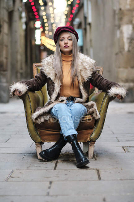 Woman with fur jacket sitting on armchair at alley — Stock Photo