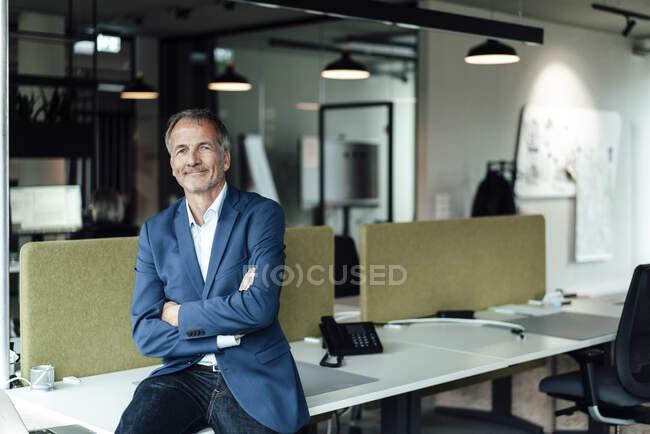 Lächelnder Geschäftsmann mit verschränkten Armen sitzt auf Schreibtisch im Büro — Stockfoto