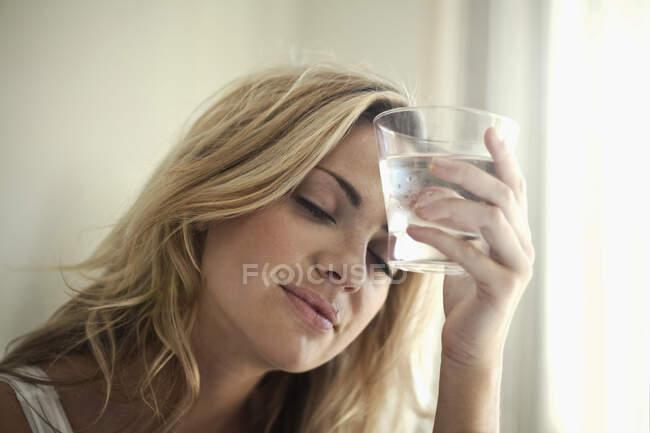 Mujer joven sosteniendo un vaso de agua contra su frente en casa - foto de stock