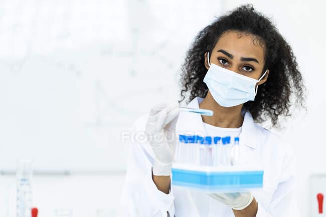 Жіночий дослідник тримає мікроплиту в лабораторії під час пандемії. — стокове фото