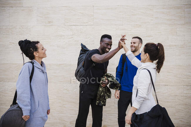 Happy male and female athlete giving high-five while standing by wall — Stock Photo