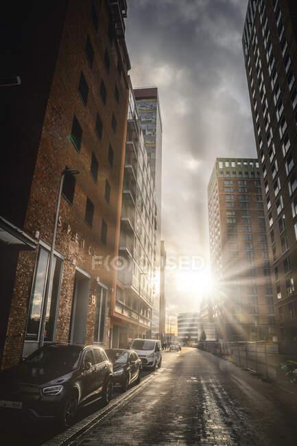 Германия, Северный Рейн-Вестфалия, Дюссельдорф, Солнце садится над машинами, припаркованными вдоль пустой городской улицы — стоковое фото