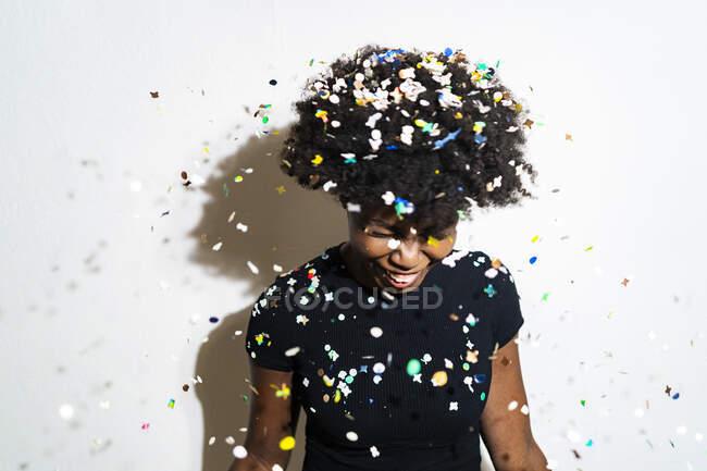 Donna sorridente con coriandoli che cadono sulla testa in piedi su sfondo bianco — Foto stock
