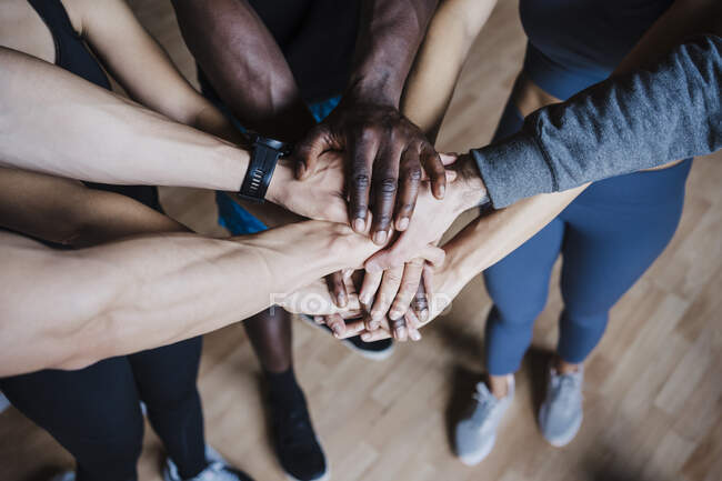 Multi-ethnic group of friends huddling while standing in gym — Stock Photo