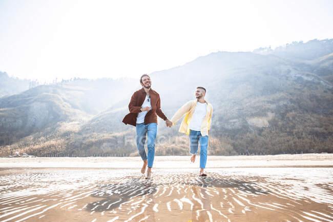 Feliz pareja gay corriendo juntos en la playa - foto de stock